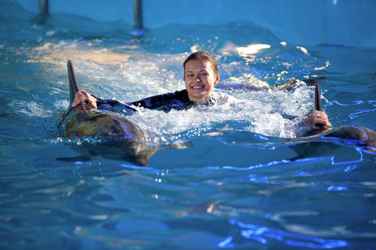Young smiling woman holding dolphin fins and swimming in pool