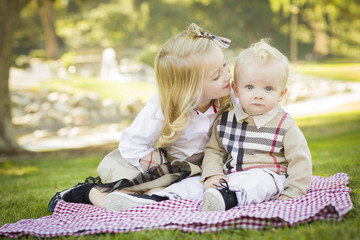Sweet Little Girl Kisses Her Baby Brother at the Park.