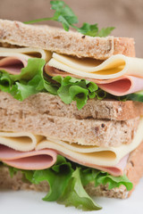Fresh ham and cheese on white sandwich in rustic kitchen setting