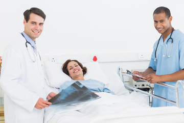Doctors with x-ray by female patient in hospital