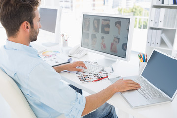 Male photo editor working on computer in a bright office
