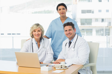 Smiling doctors with laptop at medical office
