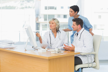 Doctors using computer together at medical office