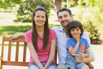 Smiling couple with son sitting on park bench