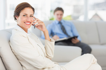 Happy businesswoman on the phone sitting on couch
