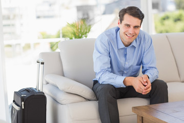 Smiling businessman sitting on couch waiting to leave on busines