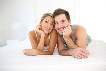 Portrait of cheerful young couple laid on bed