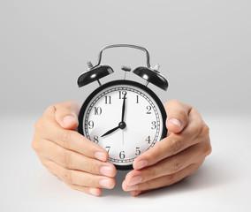 man holding alarm clock in hands
