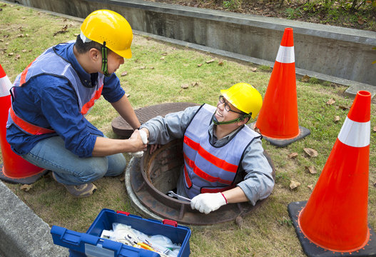 two sewerage workers in the manhole