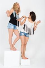 Girls having fun standing on white cubes in studio