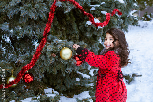 Decorating Christmas Trees Outside.Little Girl In Decorating Christmas Tree Outside Stock