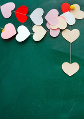 Valentine's day. Heart of paper hanging on blackboard background