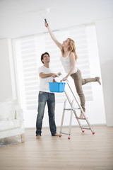 Young couple decorating her new home