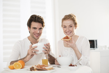 young couple takes breakfast in kitchen