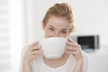 closeup young woman drinks in a big mug at breakfast
