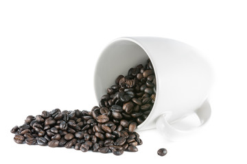 Spilled coffee beans on white ceramic cup