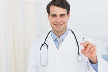 Portrait of a handsome doctor holding an injection