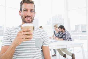 Man holding disposable coffee cup with colleagues in background