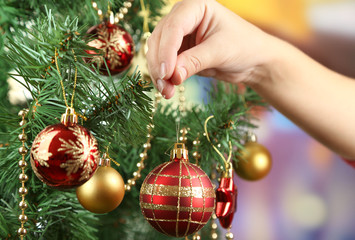 Decorating Christmas tree on bright background