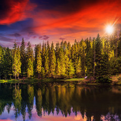 Mountain lake in coniferous forest on red sunset