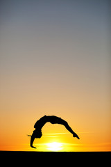 Fototapete - silhouette of female gymnast in sunset
