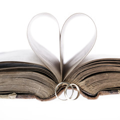 Gold wedding rings,old book and paper heart