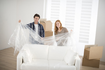smiling couple unpacking sofa in new home
