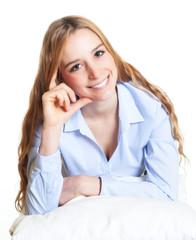Frau mit langen blonden Haaren auf einem Kissen denkt nach