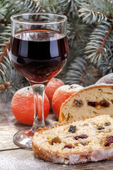 wine glass with fruit cake,  mandarin and apple in winter decor