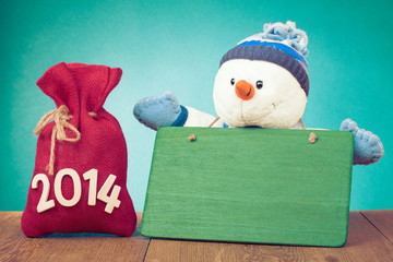 New Year greeting card with snowman and gifts bag