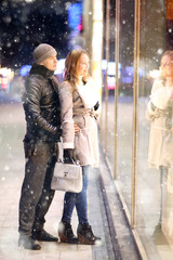 Love man and woman embracing outdoors winter snowfall