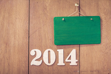 New Year number and signboard on wood background