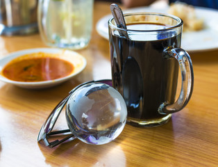 Earth transparent glass with cup of coffee and sun glasses