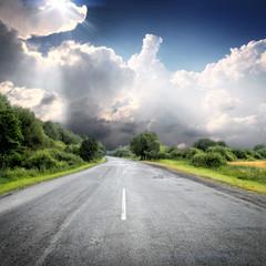 asphalt road near green fields