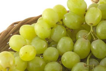 Ripe grape bunches in brown wicker basket isolated close up