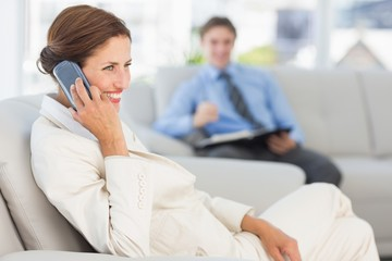 Smiling businesswoman on the phone sitting on couch