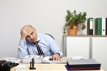 Geschäftsmann sitzt lustlos & frustriert über seinen Unterlagen