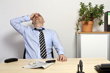 Geschäftsmann sitzt nachdenklich am Schreibtisch