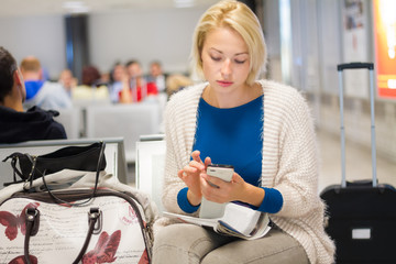 Woman using a cell phone while waiting.