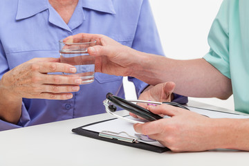 Doctor giving glass of water