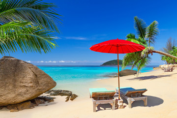 Tropical beach scenery with deck chairs in Thailand