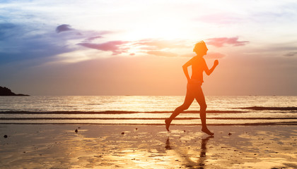 Silhouette of woman jogger at sunset on the seashore