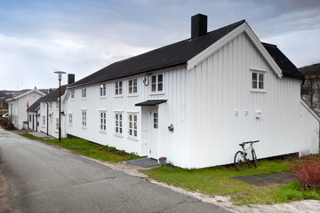 Street with small white wooden houses in Norwegian town