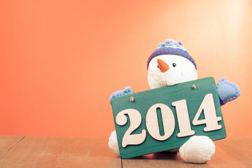 New Year greeting card with snowman and date signboard
