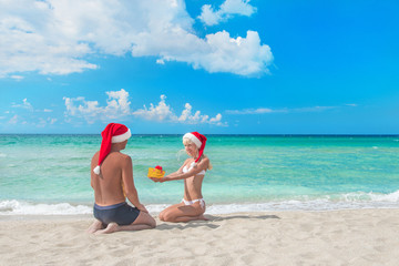 woman in santa hat  giving a present to her boyfriand on the sea