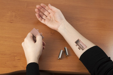 Batteries inserted into a hand. Creative idea