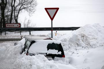 Snowbank at road stops car.