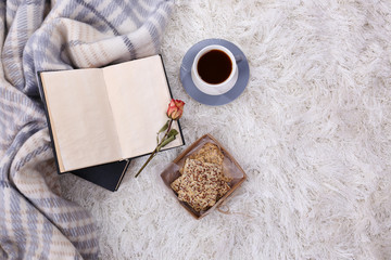 Composition with warm plaid, book, cup of hot drink