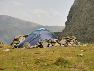 Alpine tent and  windbreak  from rocks