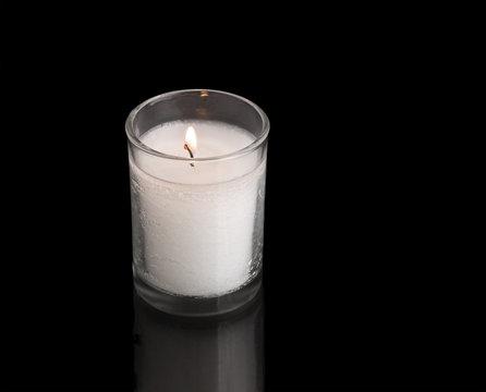 Jewish memorial yahrzeit candle light, isolated on black
